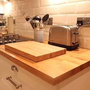 Eiche-Arbeitsplatten in einer Küche mit massivem Eiche-Schneidebrett.