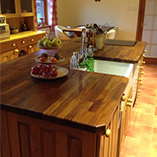 Iroko-Arbeitsplatte-Kücheninsel mit Belfast-Spüle.