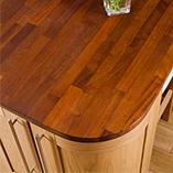 Eine Iroko-Kücheninsel-Arbeitsplatte mit großen Radius-Ecken, passend zu den kurvigen Küchenschränken.