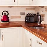 Iroko-Arbeitsplatten mit einem weichen Kantenprofil und kleiner Radius-Ecke in einer modern gemischten Küche.
