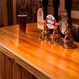 Unsere Iroko Arbeitsplatten mit durchgehenden Lamellen wurden als perfekte Thekenoberfläche für diesen Pub ausgewählt, sie haben nicht nur einen warmen Farbton, sondern sind auch noch natürlich hygienisch und wasserbeständig.