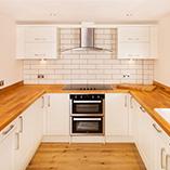 Kirschbaum Arbeitsplatten sorgen für eine warme Oberfläche, die jeder Küche einen großartigen Charakter verleiht - auch in Kombination mit hellem Weiß wie bei dieser Küche.