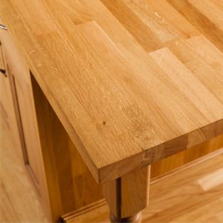 Eine Kücheninsel mit überragenden Eiche-Arbeitsplatten, die eine kleine Frühstücksbar schaffen.