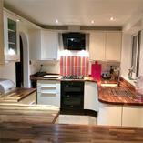 Eine Auswahl an Nussbaum-Arbeitsplatten mit vielen kurvigen Radius-Ecken und weichen Kantenprofilen passen perfekt zu glänzend kurvigen Küchenschränken.