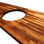 Nussbaum-Arbeitsplatte mit Ausschnitt für eine Einbauspüle und Ablaufrillen an beiden Seiten der Spüle.