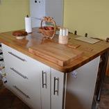 Kücheninsel mit Premium-Eiche-Arbeitsplatte und Eiche-Schneidebrett.