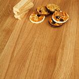 Eine Nahaufnahme der Premium Eiche Tischplatte durchgehende Lamellen. Die ebenmäßige, nahezu makellose Oberfläche kommt hier besonders gut zur Geltung.