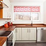 In dieser modernen Kücheneinrichtung schafft unsere Amerikanischer Nussbaum Arbeitsplatte mit durchgehenden Lamellen einen wunderschönen Kontrast zu den hellen Küchenschränken und gibt dem Raum ein luxuriöses Flair.