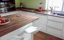 Amerikanischer-Nussbaum-Arbeitsplatten auf weiß glänzenden Küchenschränken und pastellgrünem Wandanstrich.