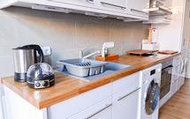 Premium-Eiche-Arbeitsplatten kombiniert mit weiß glänzenden Küchenschränken.